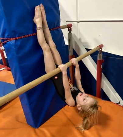 girl gymanst hanging upside down on bar with feet on mat