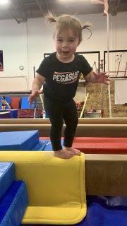young girl standing on balance beam