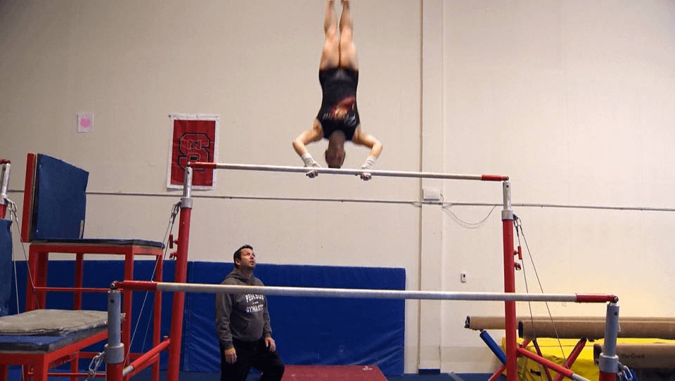 female gymnastics athlete on bars with coach watching