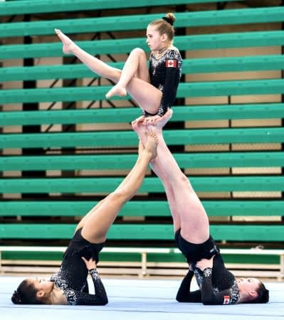 two female gymnasts balancing another girl gymnast on thier feet