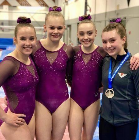 four female gymnastics in club leotards and team jacket