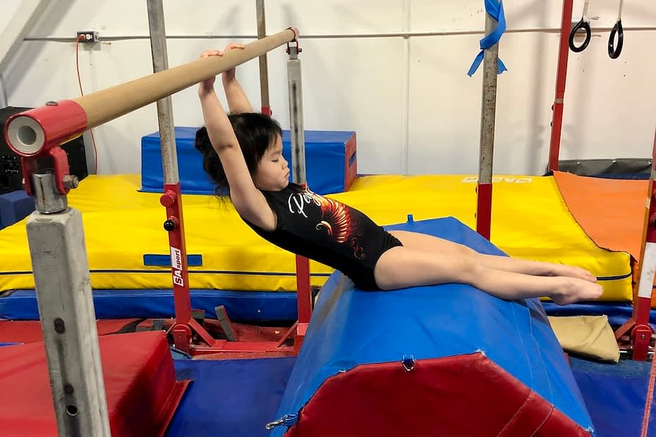 young girl hanging on bar with feet on cylinder mat