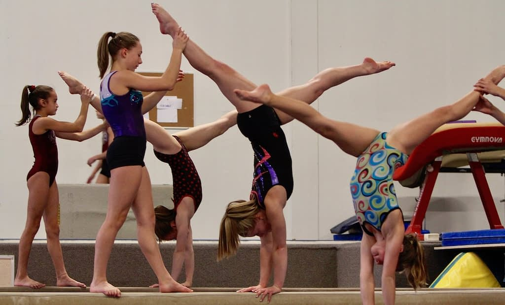 girl gymnasts on beam in handstand