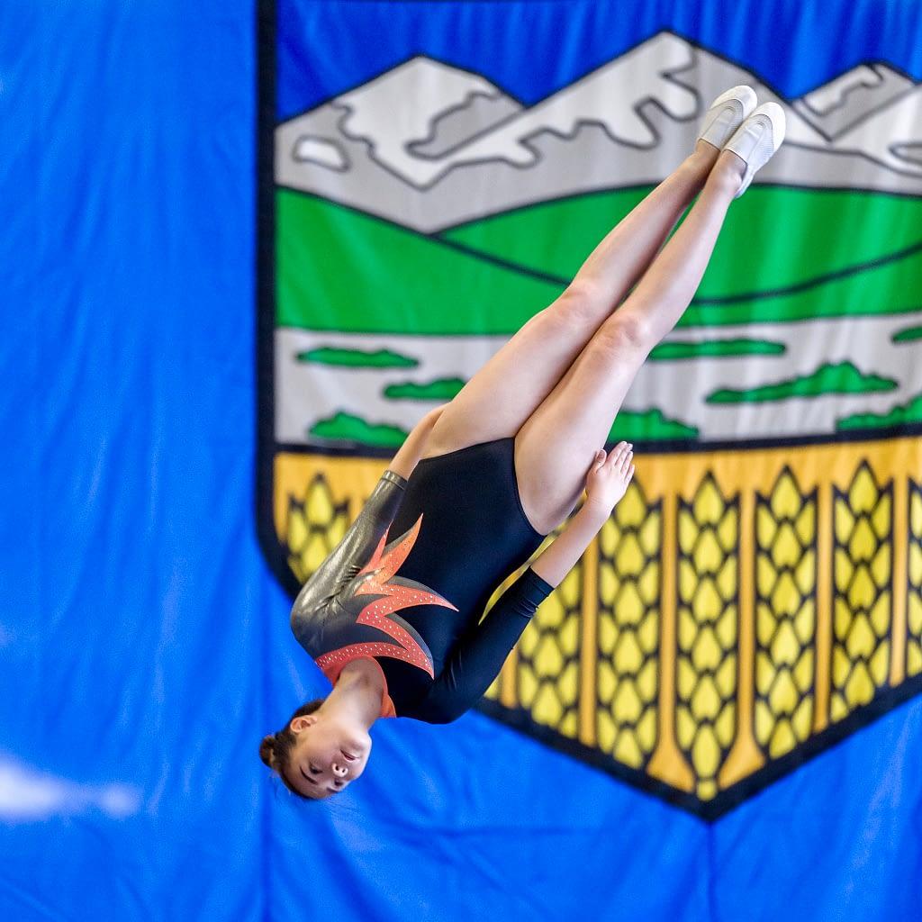 girl gymnastics flipping infront of alberta flag
